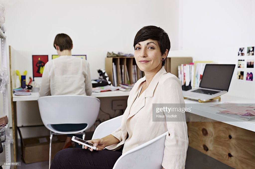 Portrait of creative businesswoman holding phone