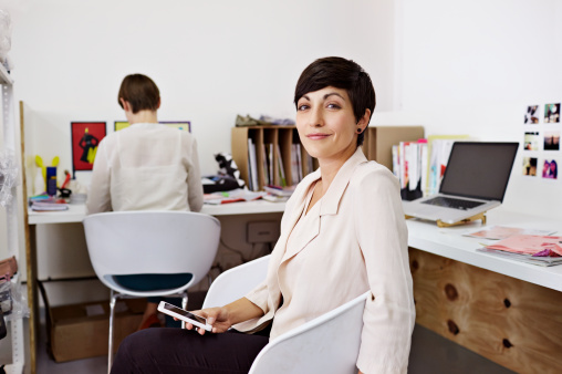 Portrait of creative businesswoman holding phone