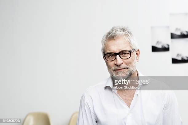 Portrait of creative grey haired man with glasses