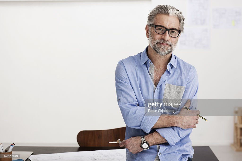 Portrait of creative mature man working on sketch : Stock Photo