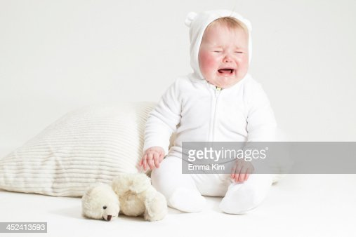 Portrait of crying baby girl and teddy bear