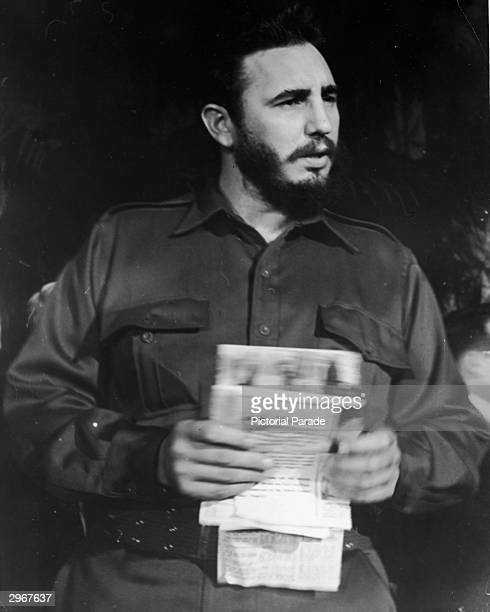 Portrait of Cuban leader Fidel Castro in uniform holding documents taken during a trip to New York City in 1959