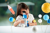 Curious little girl looking through microscope while having fun in scientific club for preschoolers, blurred background