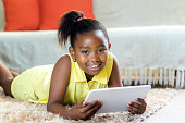 Close up portrait of cute little african girl with ponytail laying on carpet in lounge with tablet.