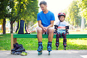 Portrait of cute baby boy with inline skating instructor in the park.