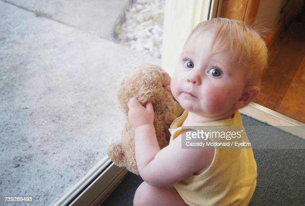 Portrait Of Cute Baby Holding Teddy Bear While Crouching In Front Of Door