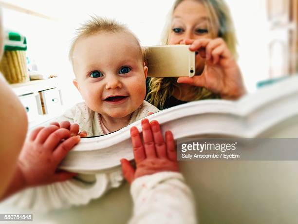 Portrait Of Cute Baby With Mother Photographing In Front Of Mirror