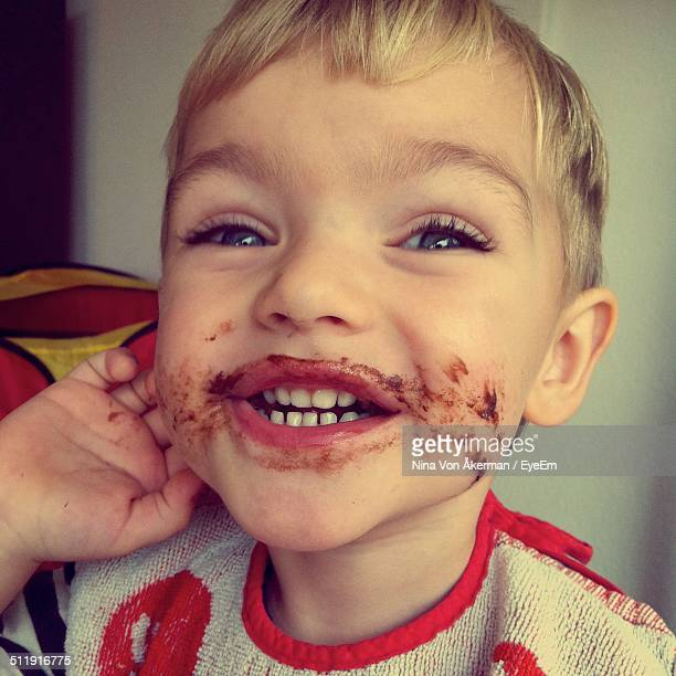 Portrait of cute boy after eating chocolate cake at home