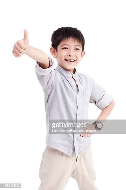 Portrait of cute boy doing thumbs up