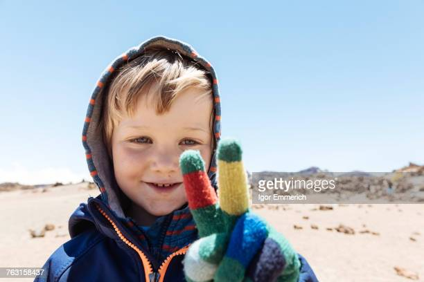 Portrait of cute boy making peace sign with gloved hand at Mount Teide, Tenerife, Canary Islands