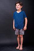 Full Length Studio Shot Of Cute Boy Standing Barefoot Against Black Background