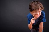 Studio Shot Of Cute Boy Against Black Background