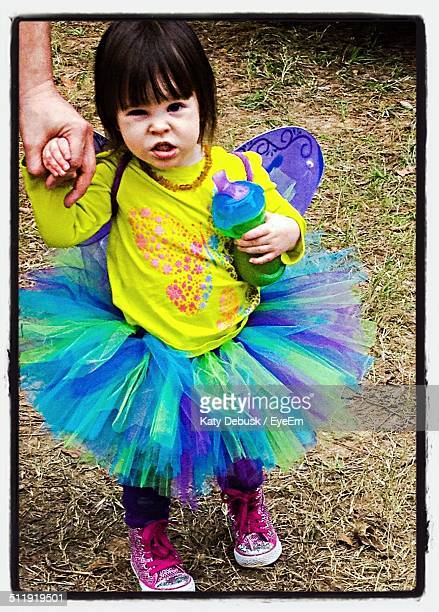 Portrait of cute girl in fairy costume holding father hand in park