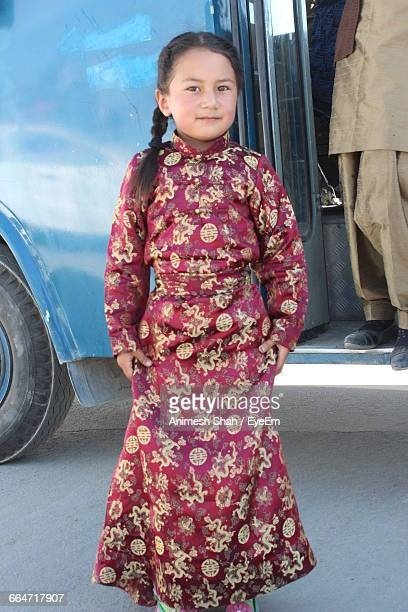 Portrait Of Cute Girl In Traditional Clothing Standing On Street