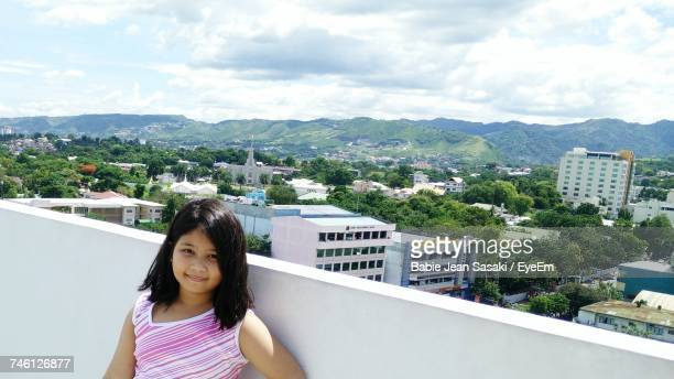 Portrait Of Cute Girl On Terrace Against Cloudy Sky
