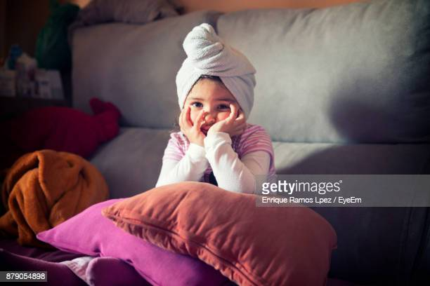 Portrait Of Cute Girl Sitting On Sofa At Home