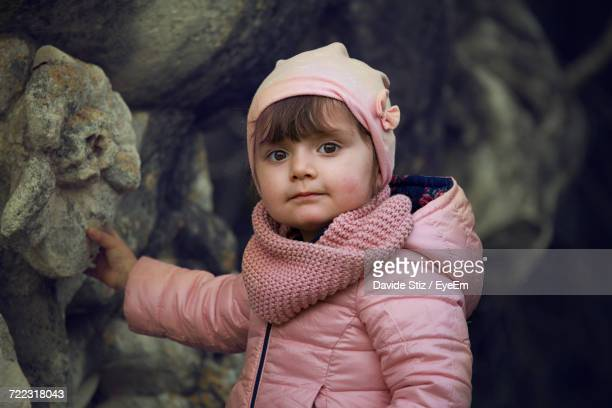 Portrait Of Cute Girl Standing By Rock Formation
