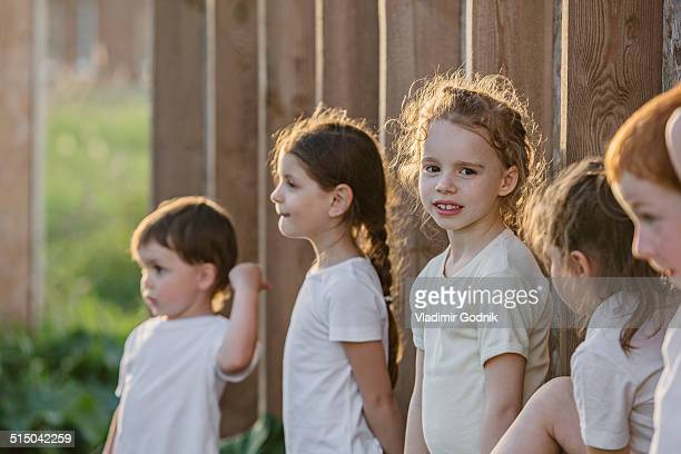 Portrait of cute girl standing with friends against wooden wall in park