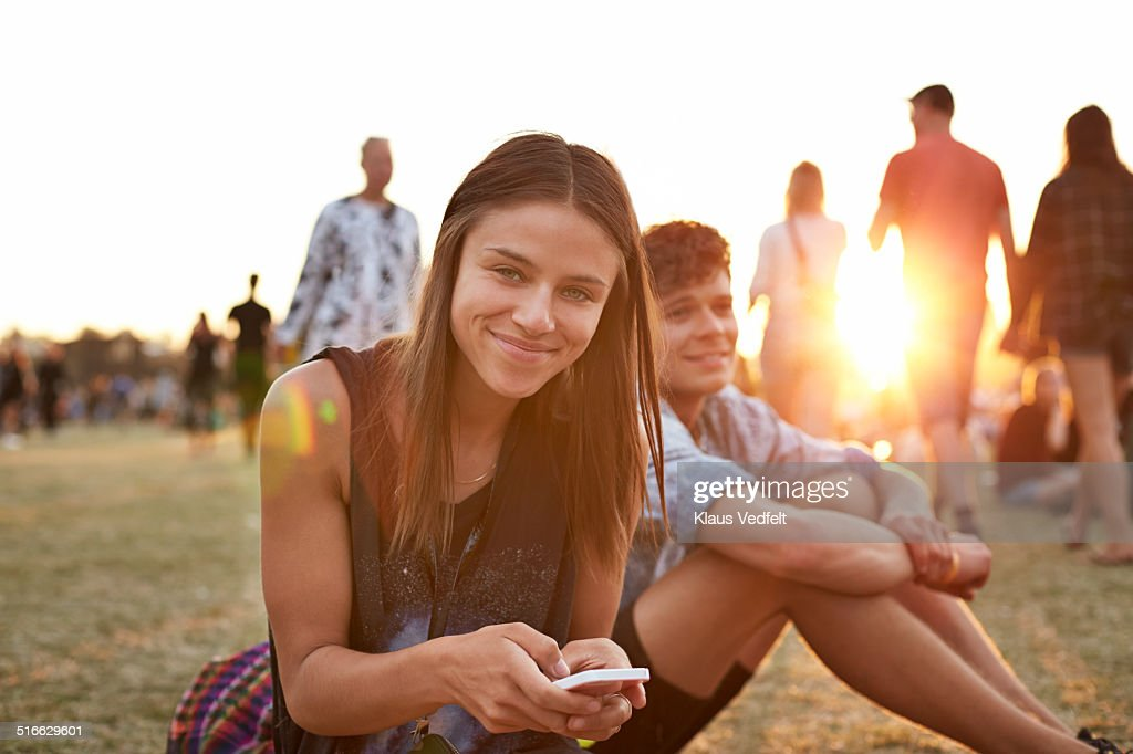 Portrait of cute girl with smartphone at festival : Stock Photo