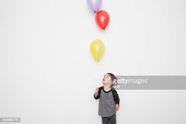 Portrait of cute male toddler holding and gazing up at three helium balloons