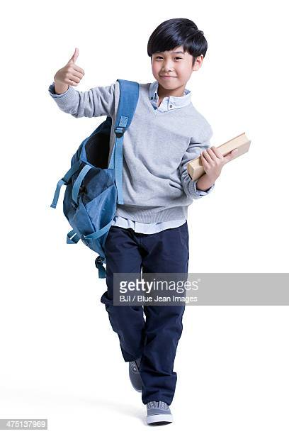 Portrait of cute schoolboy doing thumbs up
