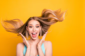 Portrait of cute straight-haired blonde caucasian smiling girl, wearing casual blue shirt, amazed, showing excitement, wind blows hair. Isolated over yellow background
