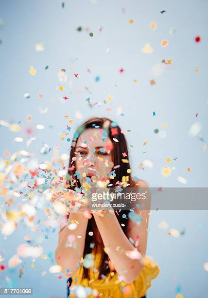 Portrait of  cute woman blowing confetti at holiday party