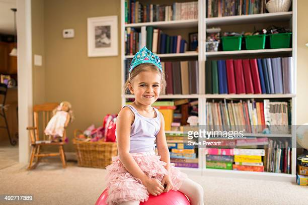 Portrait of cute young girl sitting on exercise ball