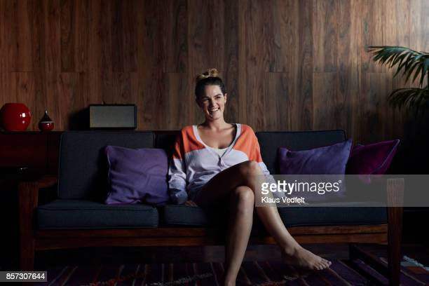 Portrait of cute young woman  sitting in couch, smiling to camera