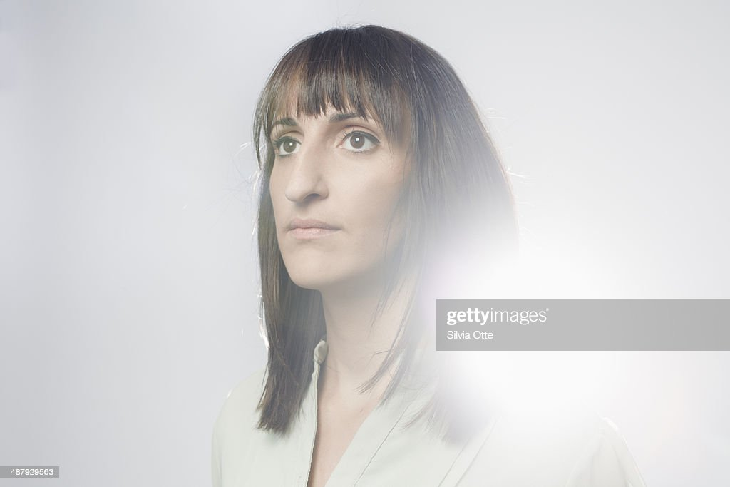 Portrait of dark haired woman in white glow : Stock Photo