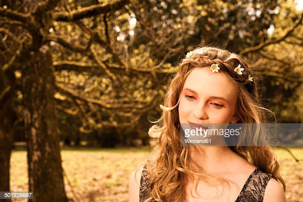 Portrait of daydreaming young woman with flowers in hair
