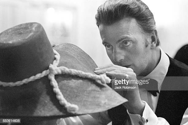 Portrait of designer Herbert de Givenchy as he adjusts his hat 20th century