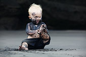 Funny portrait of smiling child with dirty face sitting and playing with fun on black sand sea beach before swimming in ocean. Family active lifestyle, and water leisure on summer vacation with baby