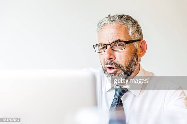 Portrait of discontent businessman working at laptop
