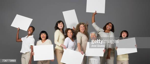 Portrait of diverse group of smiling women holding blank signs
