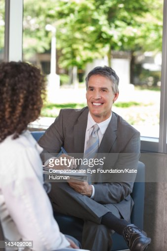 Portrait of doctor talking with colleague, smiling
