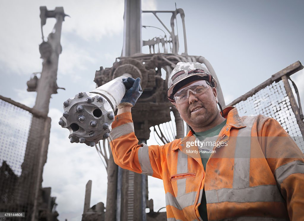 Portrait of drilling rig worker in hard hat and workwear