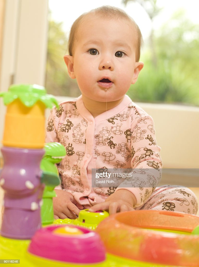 Portrait of drooling baby with toys : Stock Photo