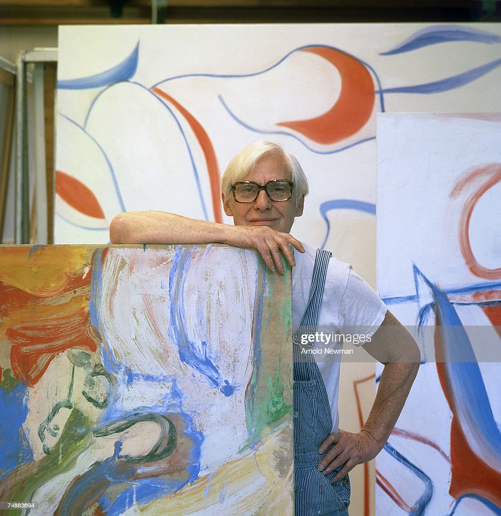 Portrait of Dutch-born American artist Willem de Kooning (1904 - 1997) as he poses in his studio, dressed in blue and white striped overalls, Springs, Long Island, New York, late October, 1983.