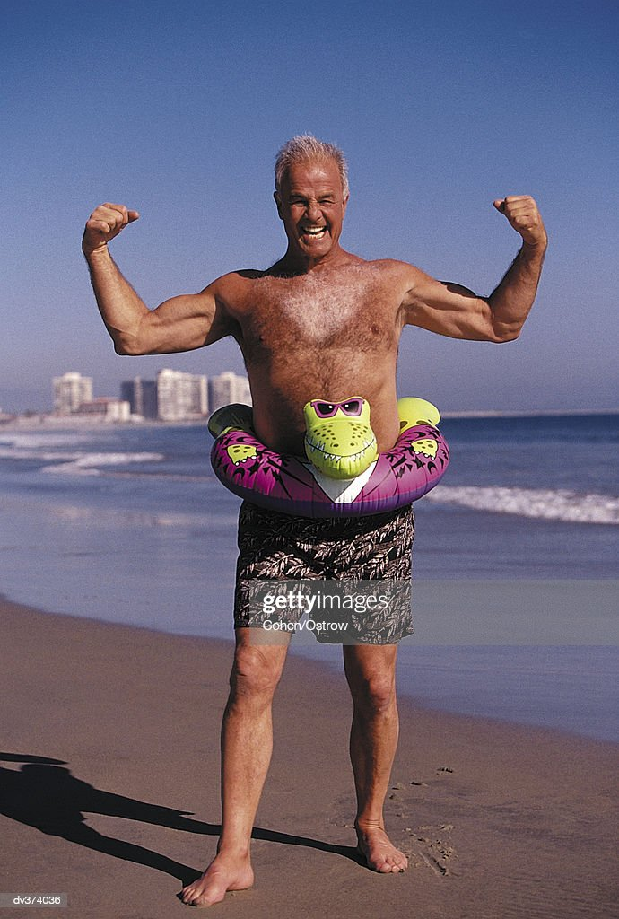 Portrait of elderly man flexing on beach : Stock Photo