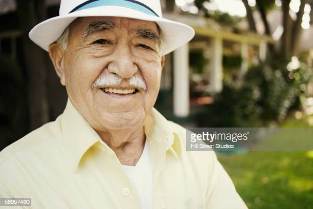 Portrait of elderly man smiling in front yard