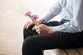 Senior man holding flowers sitting on a bench