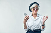 Joyful elderly woman in hipster clothes listening to music on smartphone and looking away with wide smile