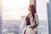 Portrait of elegant business lady wearing white formal suit standing near window looking at cityscape.