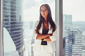 Portrait of elegant business lady wearing white formal suit standing near window looking at camera.