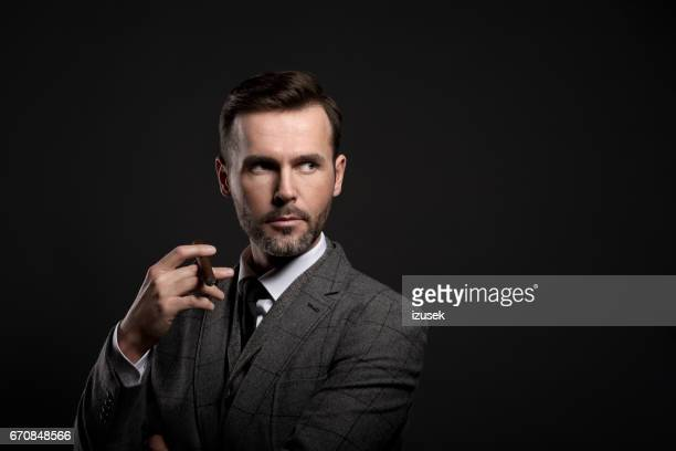 Portrait of elegant man smoking cigar