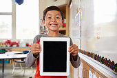 Portrait of elementary school boy holding up tablet computer