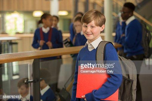 Portrait of elementary school boy wearing blue school uniform standing in school corridor