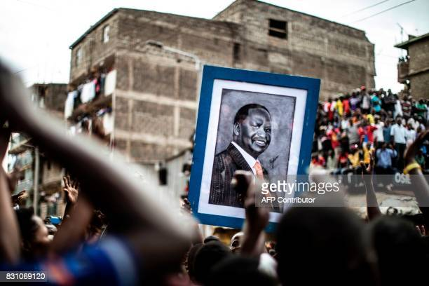 TOPSHOT A portrait of embattled Kenyan opposition leader Raila Odinga is carried by a crowd waiting for his arrival in Nairobi on August 13 2017 in...