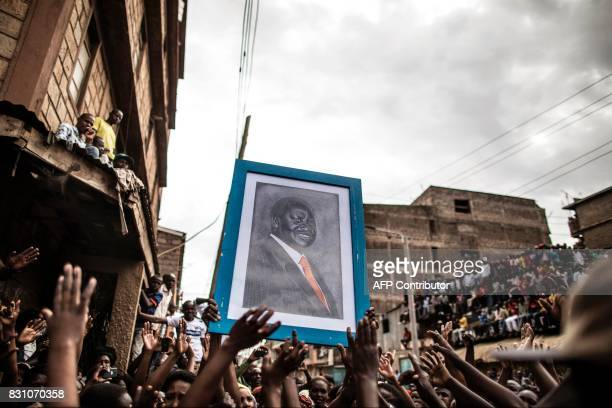 A portrait of embattled Kenyan opposition leader Raila Odinga is carried by a crowd waiting for his arrival in Nairobi on August 13 2017 in Mathare a...